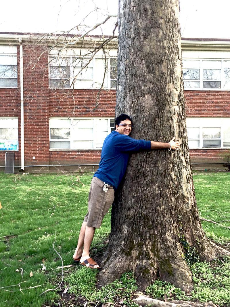 Suraj hugs his favorite sycamore